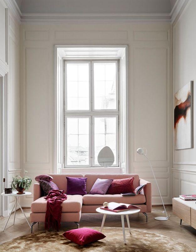 Un salon blanc adouci par un canapé rose
