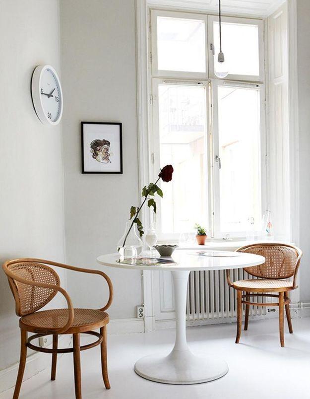 La table Tulipe mêlée à des chaises en cannage