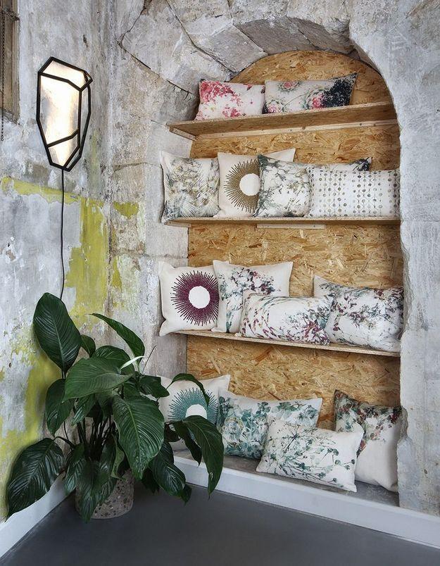 Des coussins déco du même style exposés sur des étagères