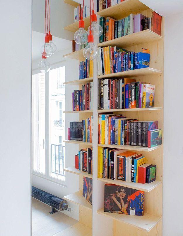 Une petite bibliothèque via des étagères collées à un miroir