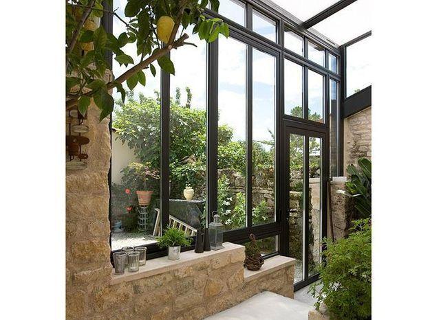 Une véranda mixant vitres et pierres