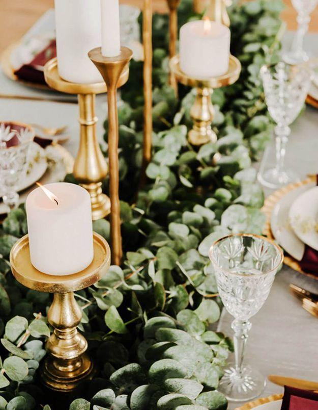 Mixer bougeoirs et branches d'eucalyptus sur la table de mariage
