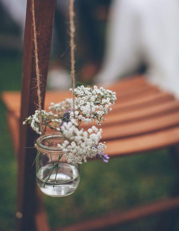 Détourner des pots de yaourt en verre en mini vases suspendus aux chaises de la cérémonie de mariage