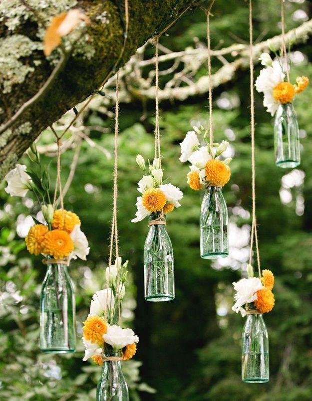 Suspendez des bouteilles en verre accueillant des mini bouquets dans le jardin