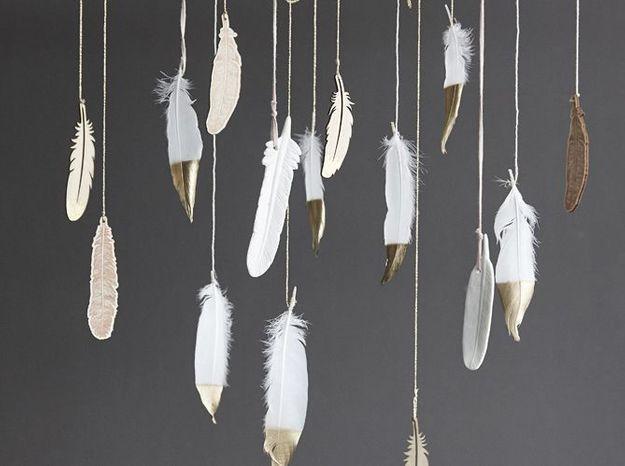 Des plumes blanches et dorées suspendues à la porte