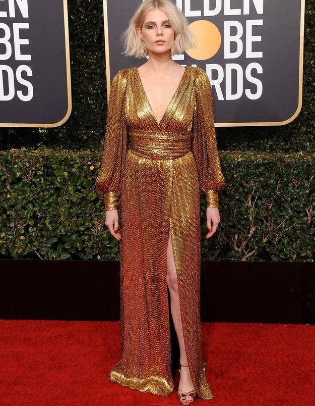 Lucy Boynton en robe décolletée or