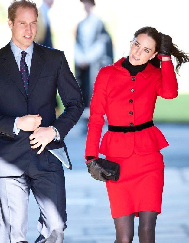 William et Kate, vêtue d'un tailleur rouge ceinturé en février 2011.