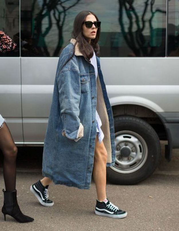 Avec un long manteau en denim