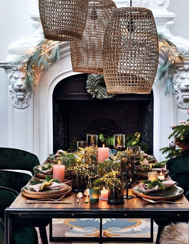 Une déco de table de Noël qui mêle branches de sapin et guirlandes lumineuses