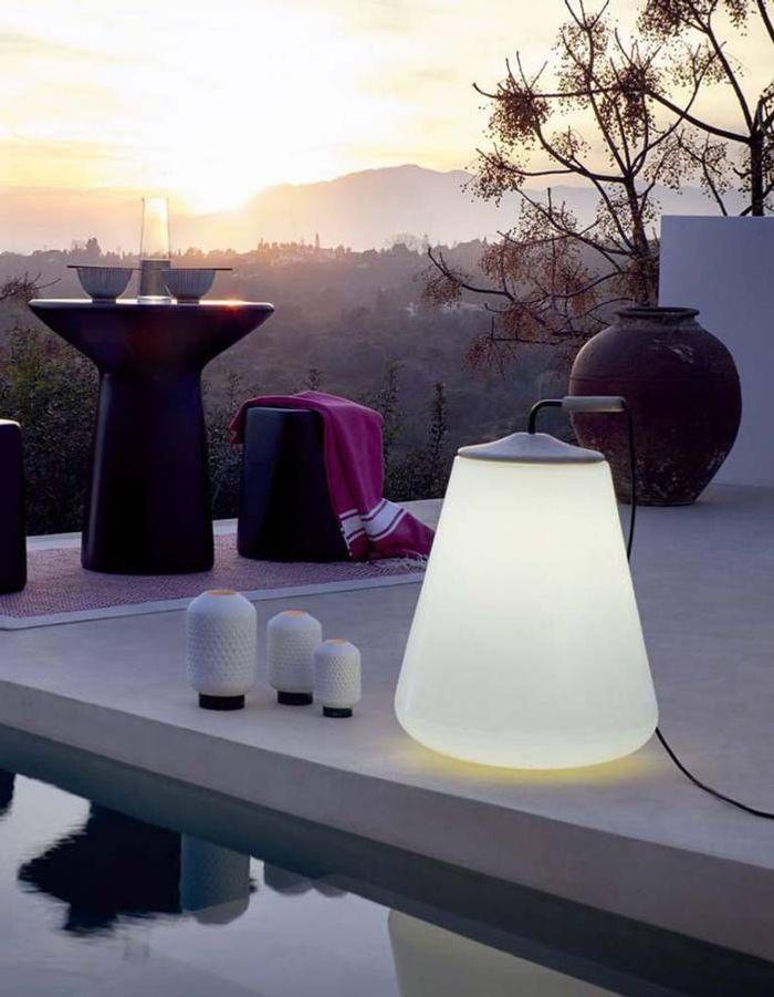 Une terrasse avec piscine éclairée par des luminaires mobiles
