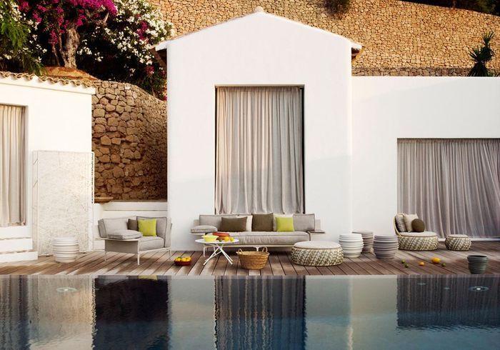 Une terrasse avec piscine qui propose différentes assises (pouf, canapé, fauteuil...)