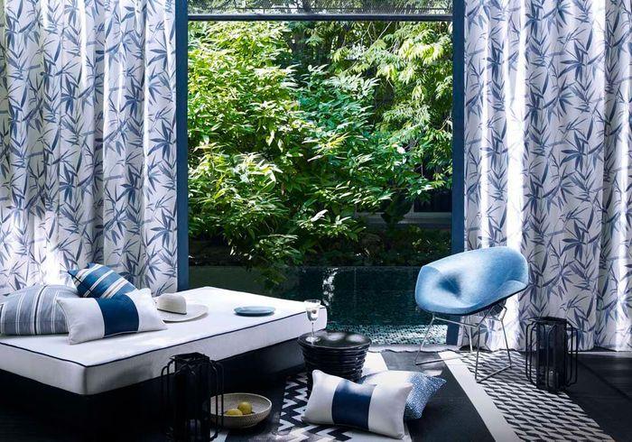 Une terrasse avec piscine séparée par des rideaux