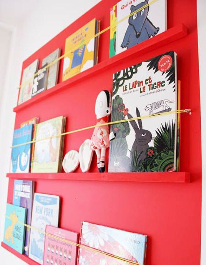 Des livres pour enfants rangés dans une étagère murale, faite d'une plaque de bois peint et des élastiques