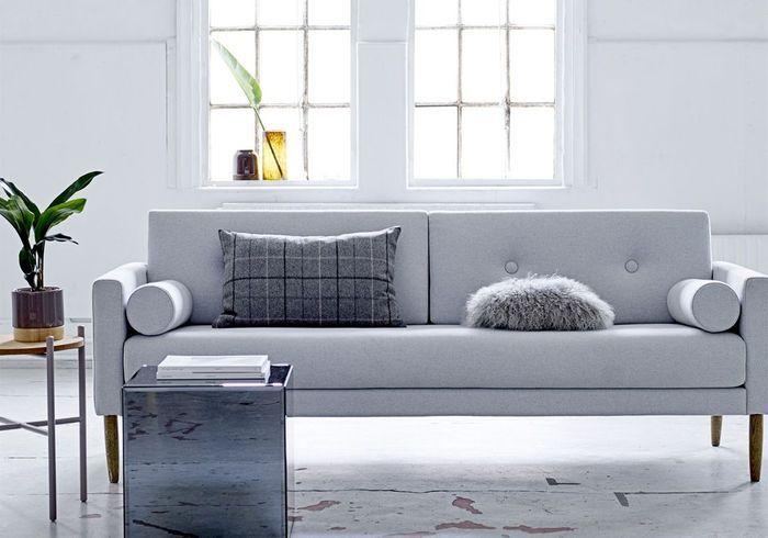 Un canapé gris accompagné d'une table basse graphique