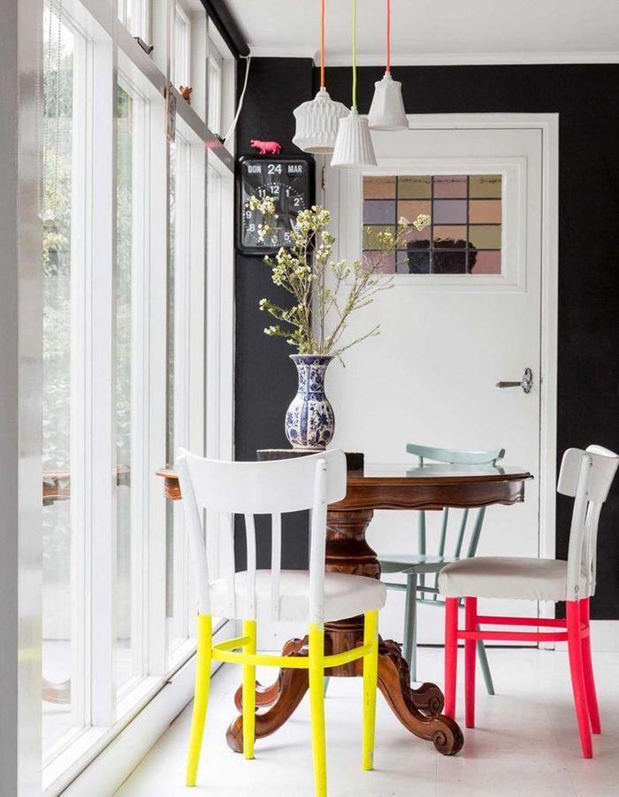 Des chaises identiques aux pieds peints dans différentes couleurs