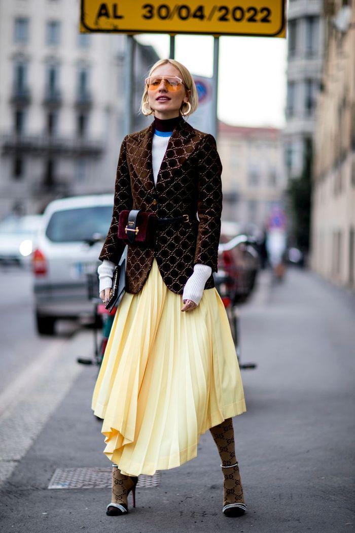 Avec des collants et une jupe plissée