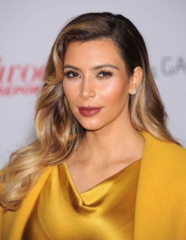 Kim Kardashian cheveux blonds et ondulés en décembre 2013