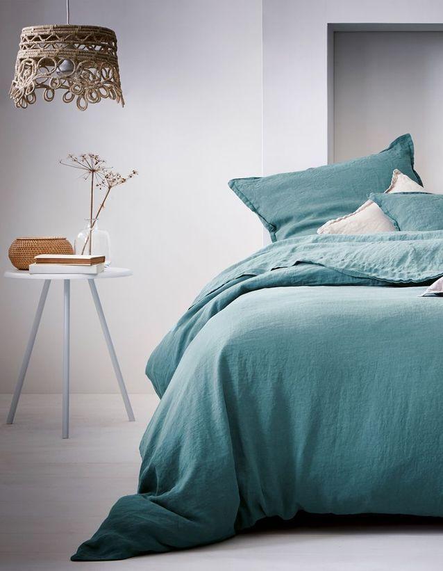 Une chambre blanche au linge de lit coloré