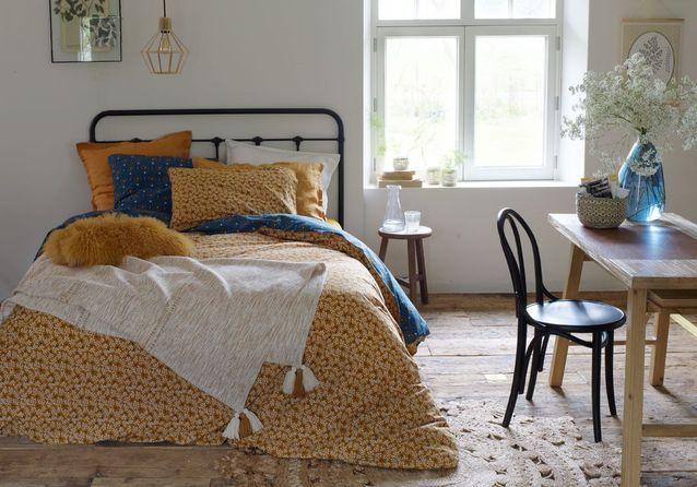 Multipliez les oreillers et les coussins sur le lit de la chambre