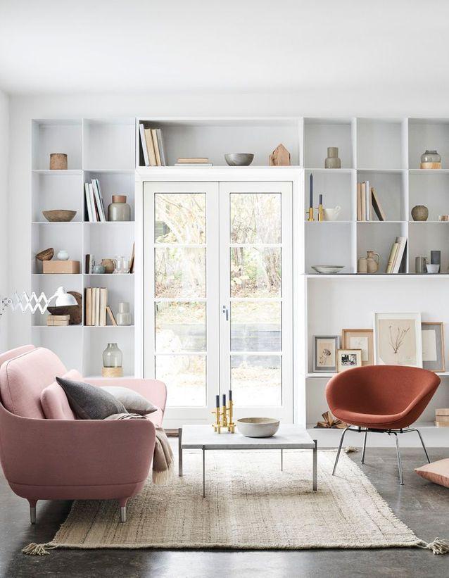 Un salon blanc animé par une grande bibliothèque