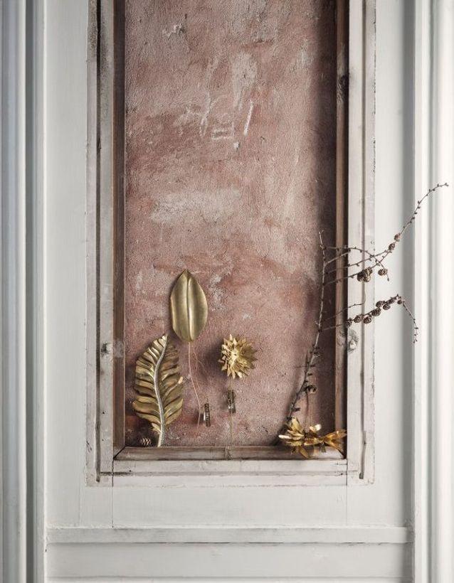Des feuilles décoratives en or pour décorer la porte à Noël
