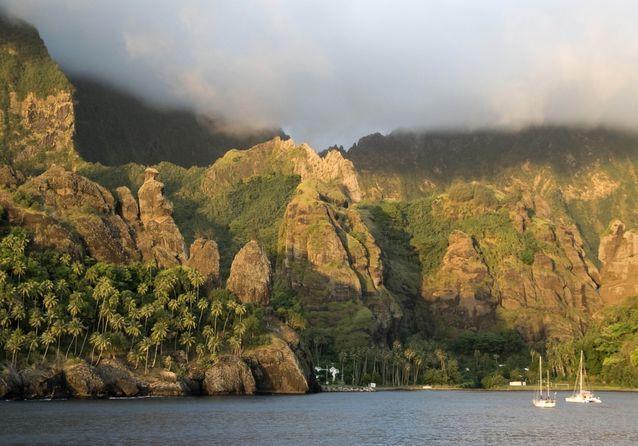 La baie de Hatiheu ses gigantesques parois rocheuses, sur lesquelles une statue de la Vierge a été érigée.