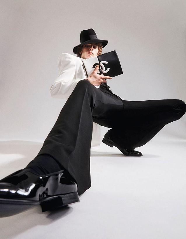 Pochette en cuir, CHANEL. Chapeau, MAISON MICHEL. Bague, STONE. Chaussures, CARVIL. Veste, chemise et pantalon, BALMAIN.