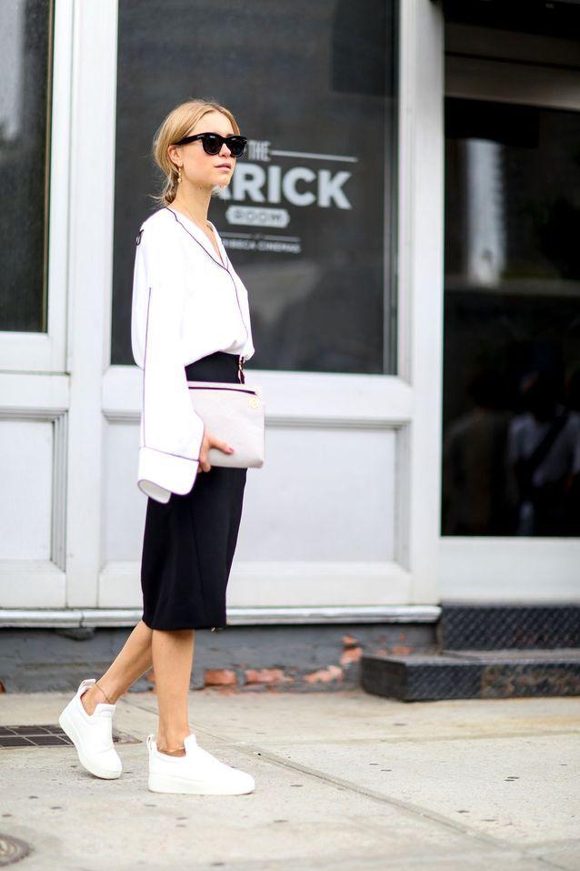Lookée en baskets avec une jupe fourreau etune blouse blanche