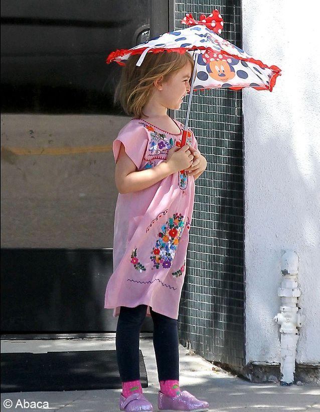 Cette petite fille se cache sous son parapluie, l'air malicieux, comme son père.