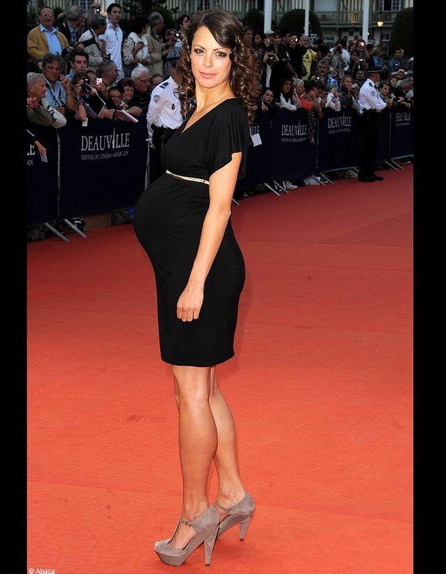 A Deauville, elle dévoile ses formes dans une petite robe noire finement serrée à la taille par une ceinture dorée.