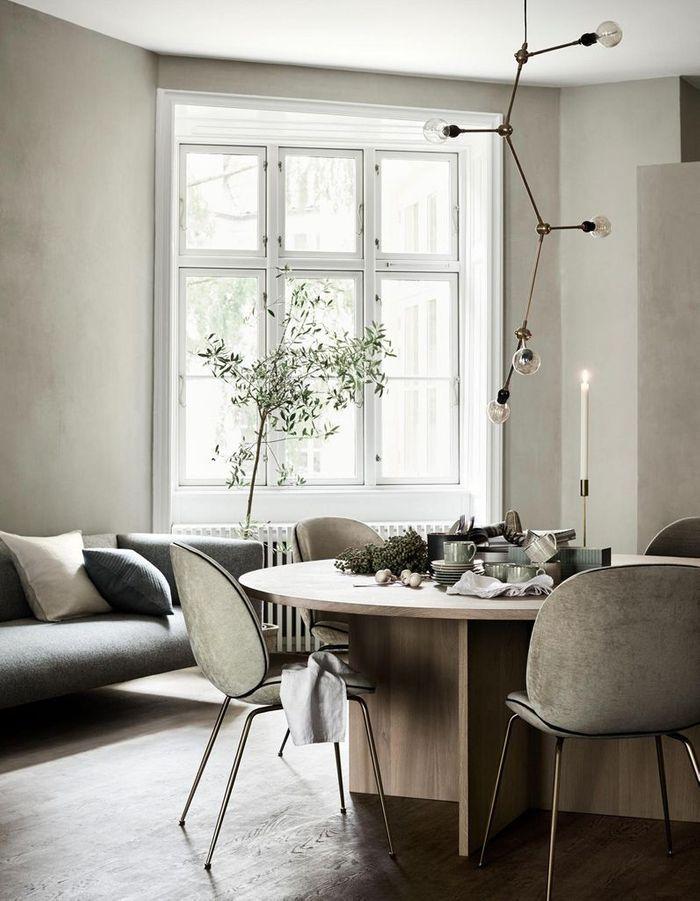 La chaise Beetle grise dans une salle à manger monochrome
