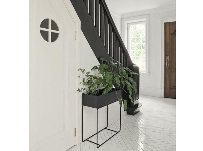 Un escalier noir pour réchauffer une entrée au total look blanc
