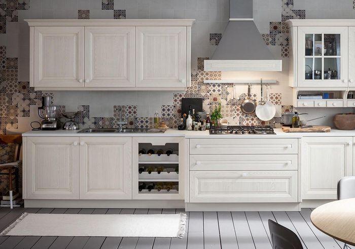 Une cuisine campagne composée de meubles en bois blanchi