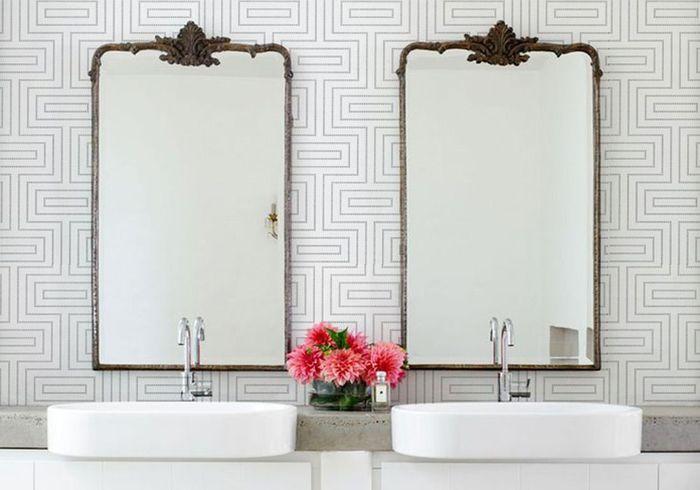 Un papier peint contemporain et des miroirs à l'ancienne pour une salle de bains dans l'air du temps