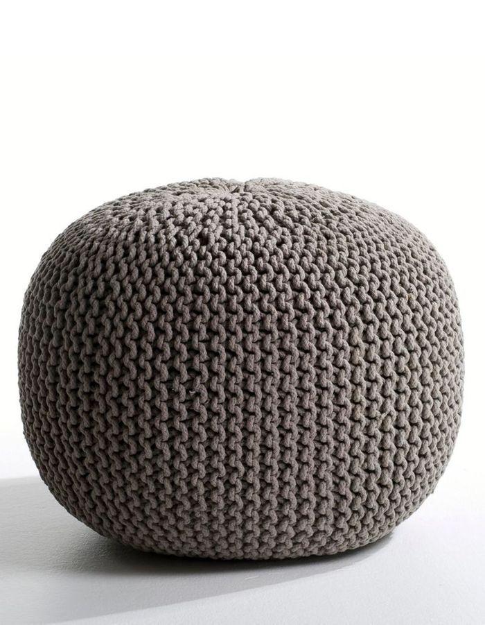 Un canapé gris accompagné d'un pouf de la même couleur
