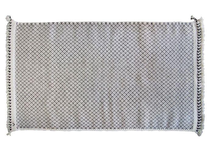 Un canapé gris accompagné d'un tapis ethnique