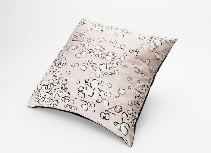 Une canapé gris accompagné d'un coussin à motifs