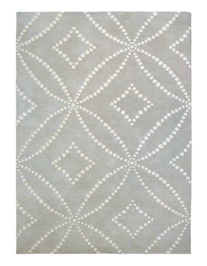 Une canapé gris accompagné d'un tapis graphique