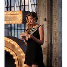Gisele Bündchen en robe courte noire, lisant un mot mystérieux