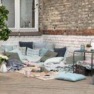 Une accumulation de coussins au sol pour relooker sa terrasse