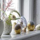 Des œufs décoratifs mêles à des vases ronds et blancs