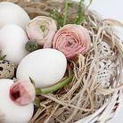 Une corbeille en osier remplie de raphia, de renoncules et d'œufs