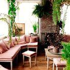 Une banquette d'angle rose entourée de végétaux