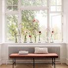 Des bouquets printaniers de différents niveaux accumulés sur le rebord de la fenêtre
