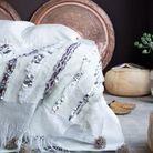 Un jeté de lit détourné en plaid ou en tenture à fixer au mur