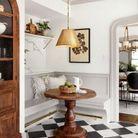 Un carrelage en damier dans un coin repas aux meubles en bois foncé
