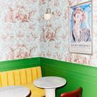 Dans la grande salle d'accueil, une des tables de petit déjeuner. Sur le mur, affiche d'une exposition de David Hockney chinée.