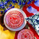Assiettes peintes à la main posées sur un tapis en laine et jute (le tout Casa Lopez).