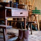 Univers rustique et poétique : bottes de pluie, moulin à moudre, table de travail et bric-à-brac de William.