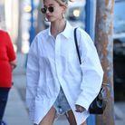 Hailey Bieber en chemise blanche et short en jean, avec son sac Celine